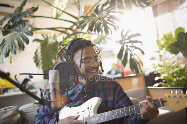 Young man recording music, playing guitar and singing into microphone — Stock Photo