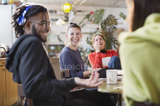 Amici di felice giovane coinquilino che ride al tavolo della cucina — Foto stock