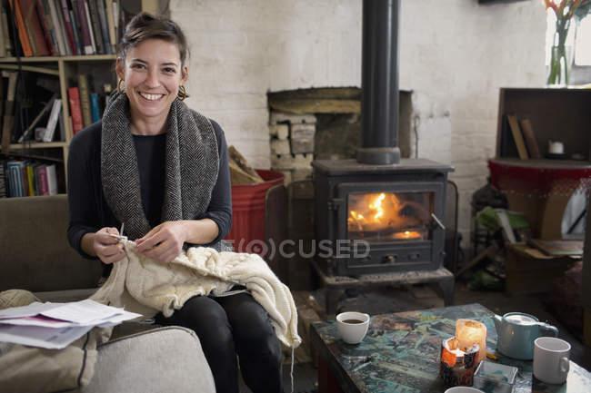 Porträt lächelnd, selbstbewusste Frau stricken Kamin im Wohnzimmer — Stockfoto