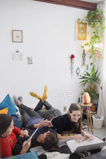 Young women friends hanging out, using laptop and digital tablet on bed — Stock Photo