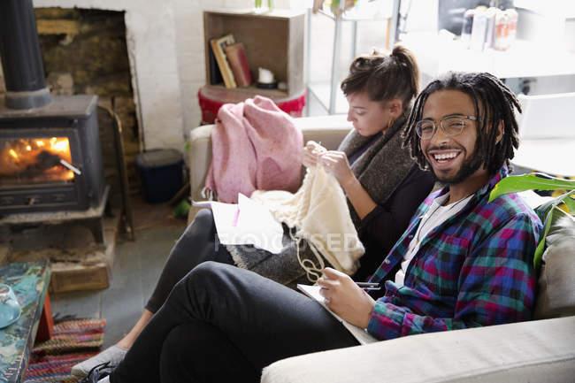 Portrait souriant jeune homme écrit dans bloc-notes sur le canapé à côté de la petite amie de tricotage — Photo de stock