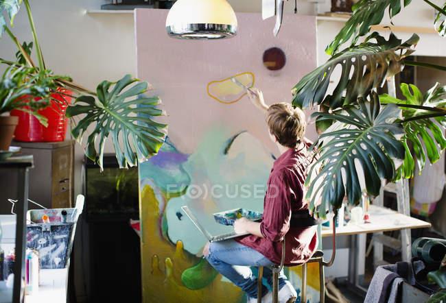 Artiste masculin, peinture sur toile grand appartement — Photo de stock