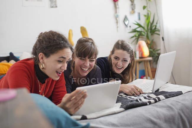 Молодые женщины друзьями болтаться, с помощью цифрового планшета и ноутбука на кровати — стоковое фото