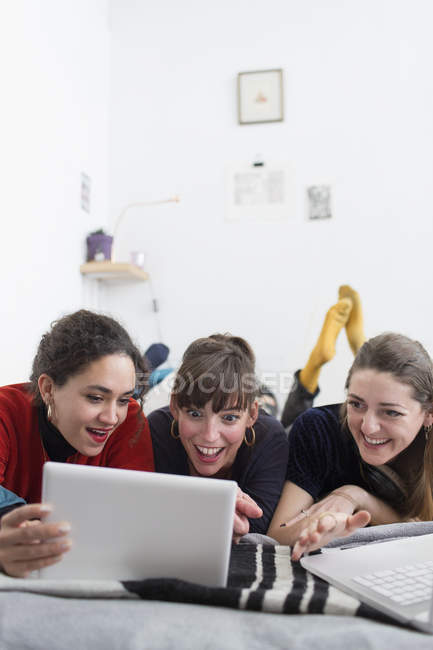 Young women friends hanging out, using digital tablet on bed — Stock Photo