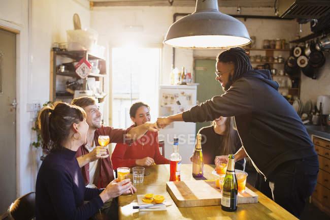 Jeunes adultes amis dégustant cocktails, poing se cogner à la table de cuisine appartement — Photo de stock