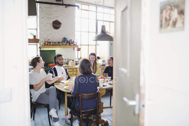 Young roommate friends drinking coffee at breakfast table in apartment kitchen — Stock Photo