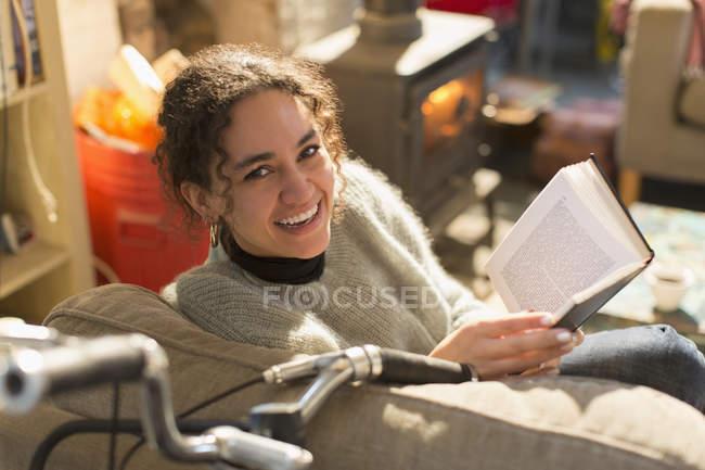 Retrato sorrindo, feliz jovem mulher lendo livro na poltrona — Fotografia de Stock