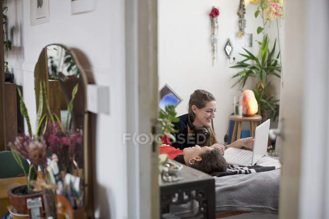 Young women friends relaxing, using laptop and digital tablet on bed — Stock Photo