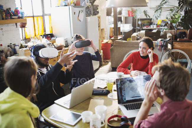 Young college student friends studying, using virtual reality simulator glasses at kitchen table in apartment — Stock Photo