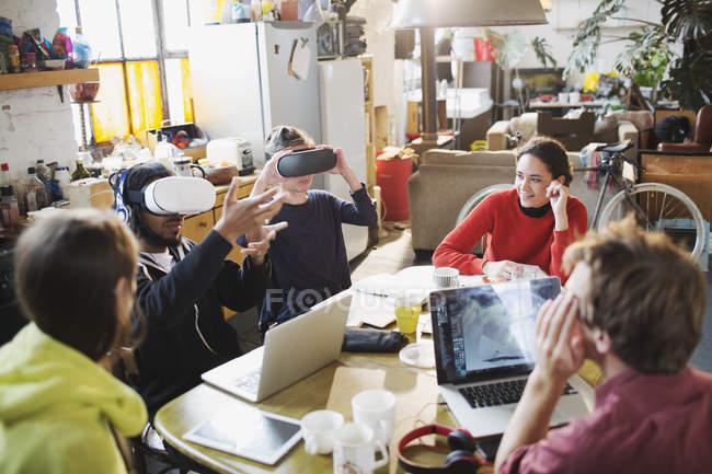 Молодий коледжу студента друзі навчаються, використовуючи віртуальну реальність симулятор окуляри в кухонному столі в квартирі — стокове фото
