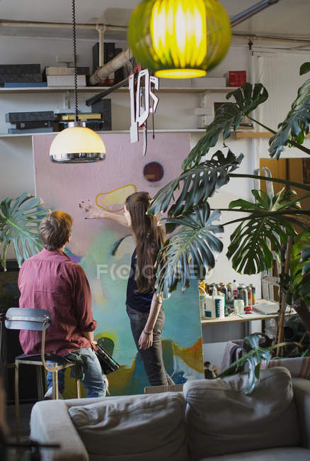 Художники обговорювати велику картину в квартирі — стокове фото
