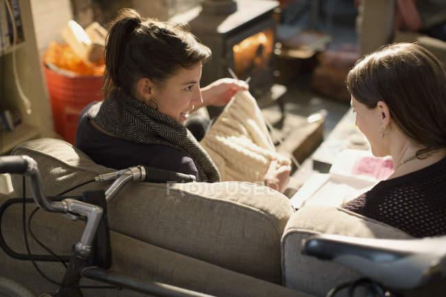 Молодые женщины соседей, вязание на гостиной диван — стоковое фото