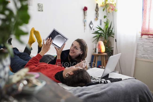 Jovens amigas relaxantes, usando tablet digital e laptop na cama — Fotografia de Stock