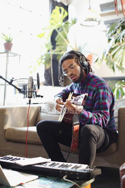 Молодой человек записывать музыку, играть на гитаре и петь в микрофон в квартире — стоковое фото