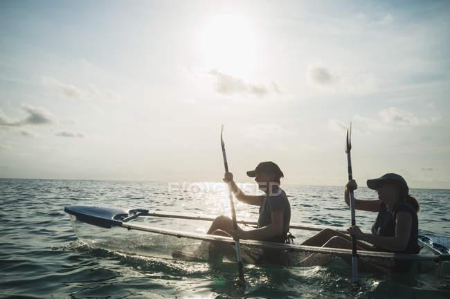 Women in clear bottom canoe on sunny ocean, Maldives, Indian Ocean — Stock Photo