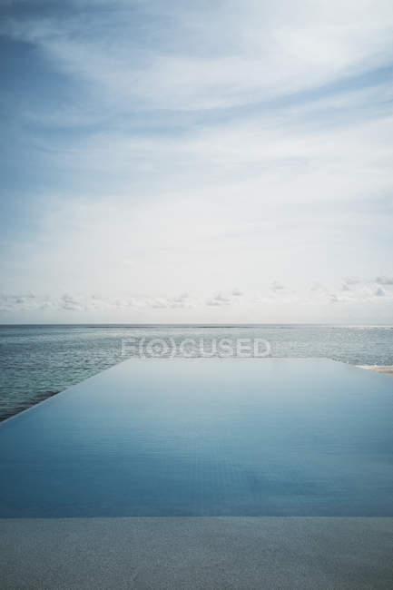 Tranquil blue infinity pool and ocean, Maldives, Indian Ocean — Stock Photo