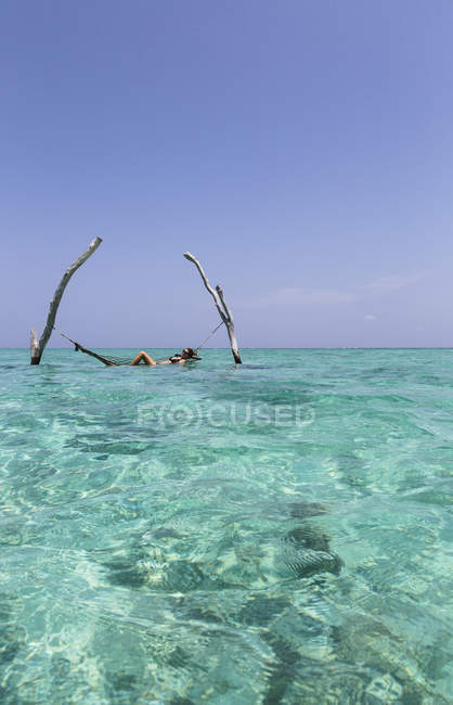 Young woman laying in hammock over tranquil blue ocean, Maldives, Indian Ocean — Stock Photo