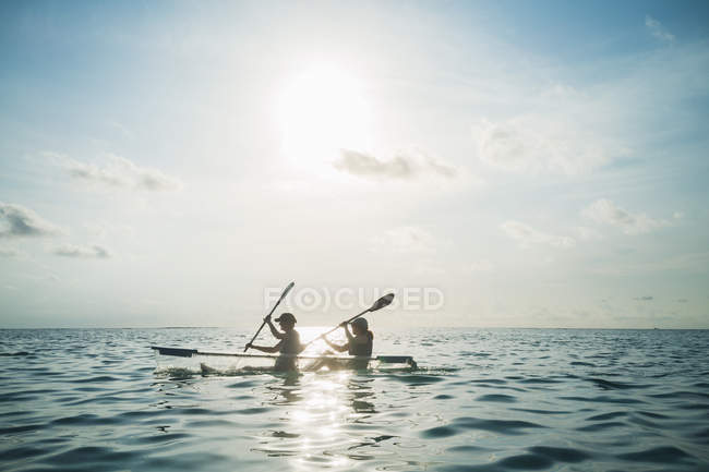 Donne in canoa di fondo chiaro sul mare soleggiata, idilliaco, Maldives, Indian Ocean — Foto stock