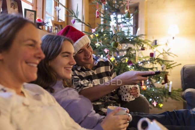 Сім'я відпочинку, дивляться телевізор в різдвяні вітальні — стокове фото