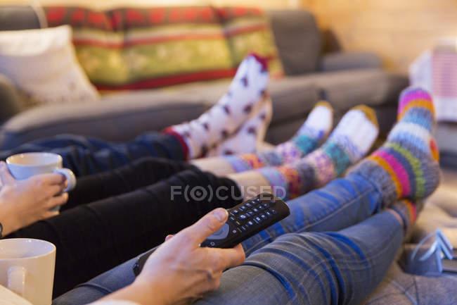 Семья в цветастой газировке расслабляется, смотрит телевизор в гостиной — стоковое фото
