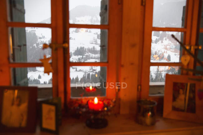 Christmas candle in window overlooking tranquil snowy landscape, Forclaz, Switzerland — Stock Photo