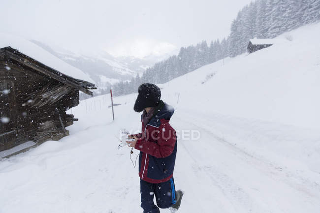 Teenage boy walking outside snowy mountain cabin, Forclaz, Switzerland — Stock Photo