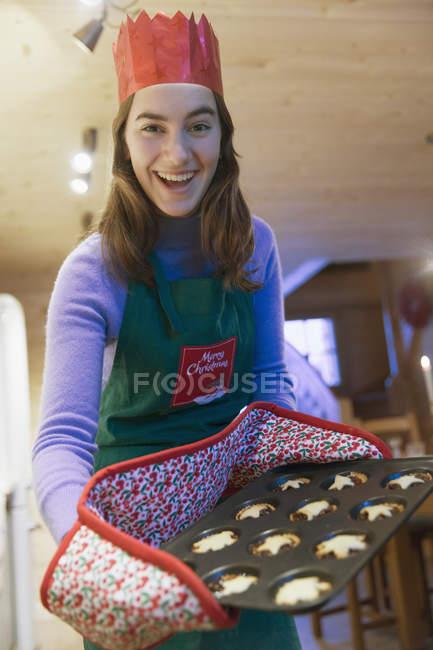 Adolescente enthousiaste de portrait dans la Couronne de tablier et de papier de Noël cuisson des muffins — Photo de stock