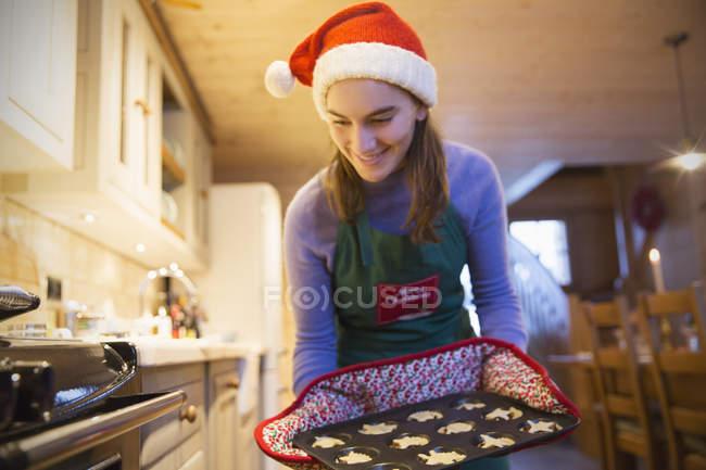 Усміхаючись Дівчинка-підліток у фартух Різдво і Санта hat випічка кекси кухні — стокове фото