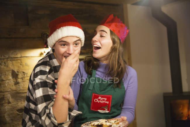 Игривые брат и сестра едят рождественское печенье — стоковое фото