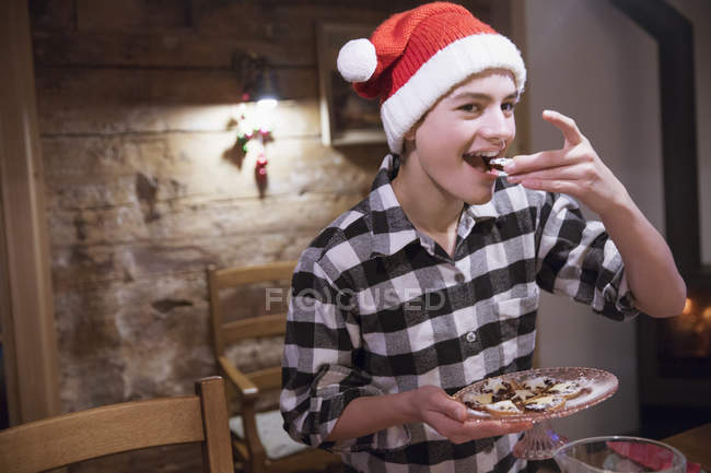 Adolescent en bonnet de manger des biscuits de Noël — Photo de stock