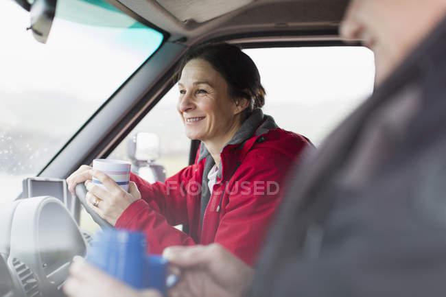 Посміхаючись жінка пити каву і водіння будинок — стокове фото