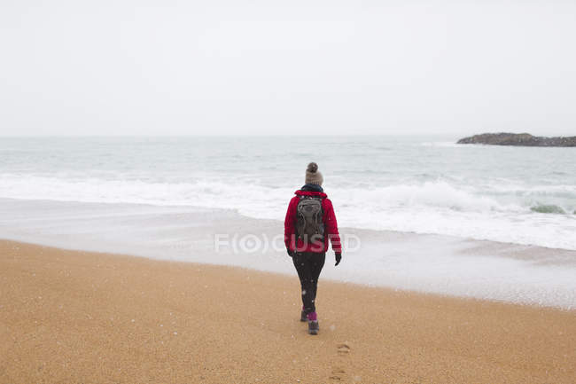 Woman with backpack walking on winter beach — Stock Photo