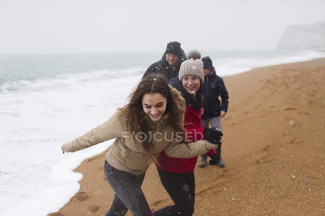 Famiglia felice e spensierata sulla spiaggia di inverno nevoso — Foto stock