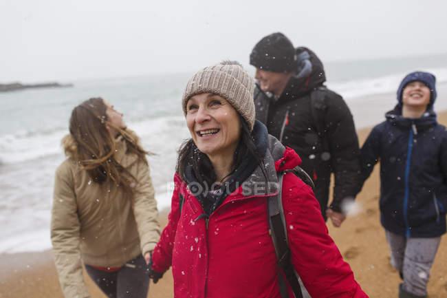 Neve che cade sopra famiglia felice sulla spiaggia di inverno — Foto stock