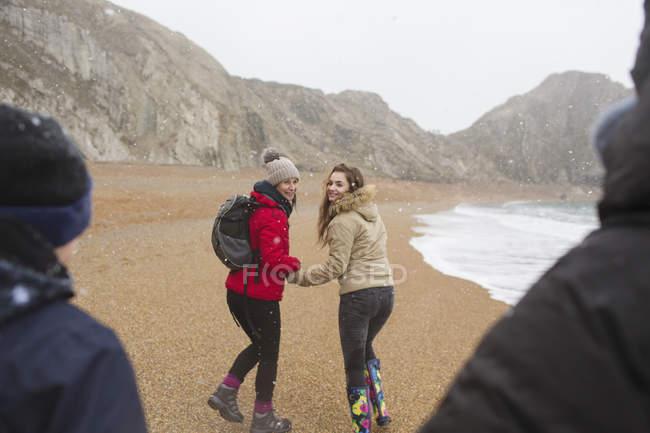 Famiglia che cammina sulla spiaggia di inverno nevoso — Foto stock