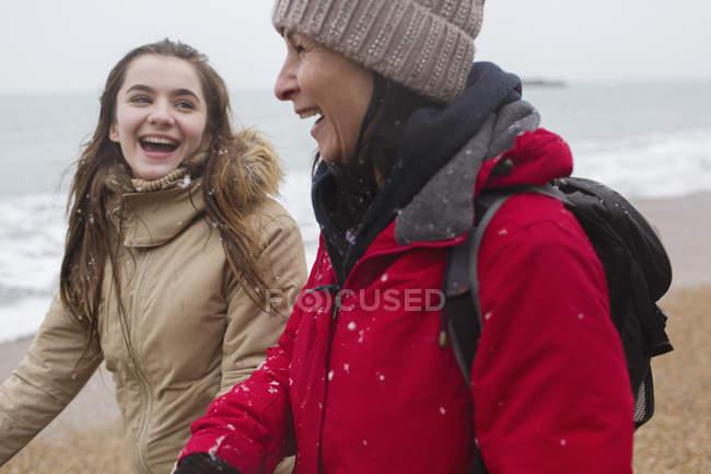 Felice madre e figlia a piedi sulla spiaggia innevata — Foto stock
