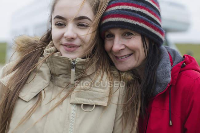 Усміхаючись, ласкава мати і дочка в теплий одяг — стокове фото