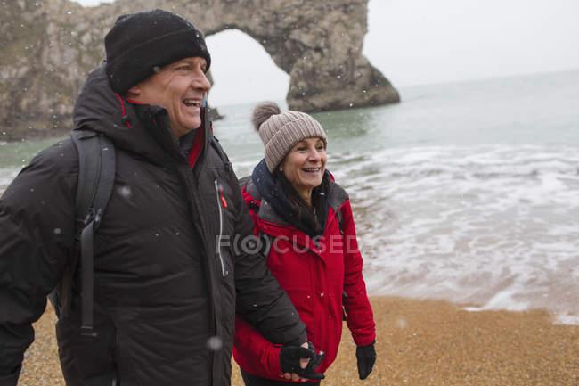 Coppia felice in abiti caldi a piedi sulla spiaggia innevata dell'oceano — Foto stock