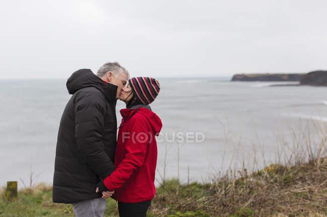 Affettuosa coppia baciare sulla scogliera con vista oceano — Foto stock