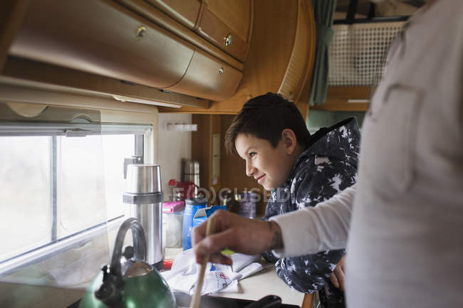 Father and soon cooking and looking out window in motor home — Stock Photo