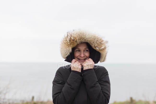 Портрет усміхається жінка в пальто з хутром капюшоном — стокове фото