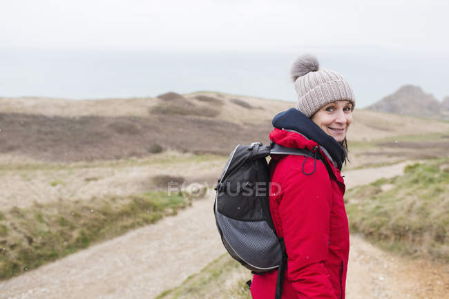 Portrait smiling woman in warm clothing with backpack hiking on remote path — Stock Photo
