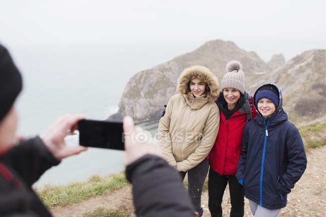 Человек с камерой телефона, фотографирование семьи в теплую одежду на скале с видом на океан — стоковое фото