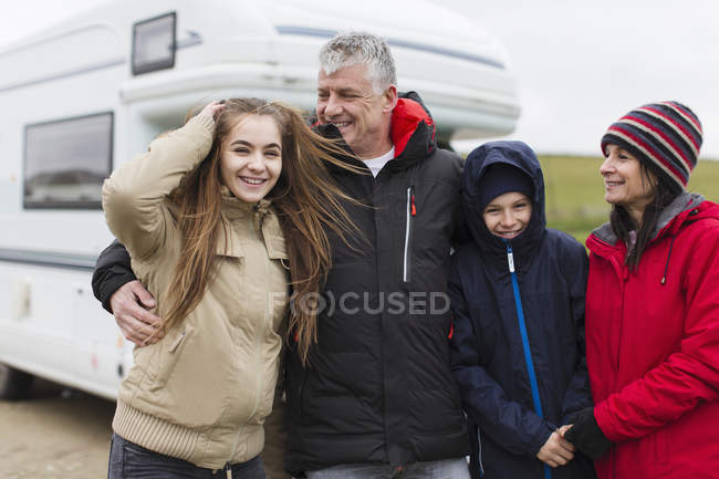 Portrait happy family in warm clothing outside motor home — Stock Photo