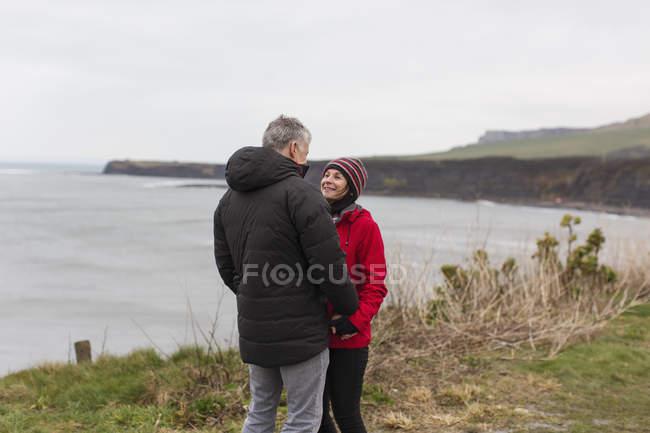 Coppia che parla sulla scogliera con vista sull'oceano — Foto stock