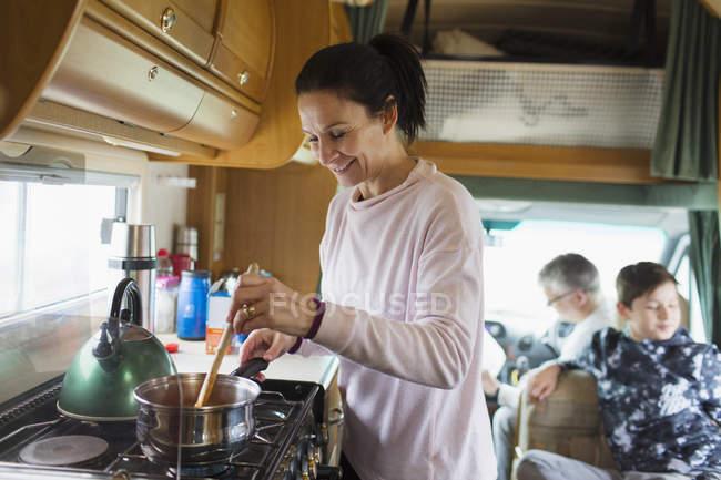 Mulher sorridente cozinhar em motor home — Fotografia de Stock