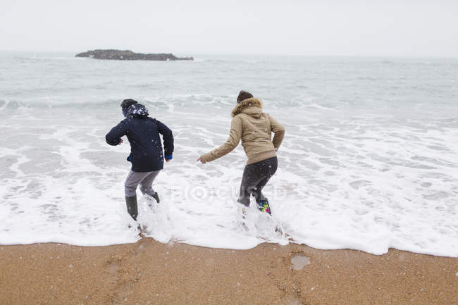 Playful teenage brother and daughter playing in winter ocean surf — Stock Photo