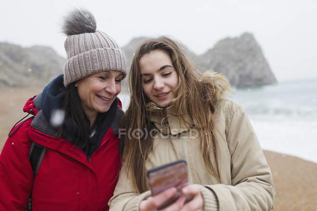Madre e figlia in abiti caldi utilizzando lo smartphone sulla spiaggia invernale innevata — Foto stock