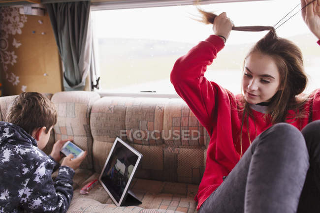 Adolescente irmão e irmã relaxante, usando tablet digital e telefone inteligente em casa motor — Fotografia de Stock