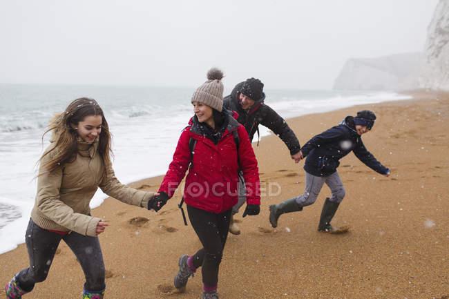 Famiglia allegra in abbigliamento caldo sulla spiaggia di inverno nevoso — Foto stock